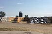 Two tractors with loaders building a silage pile.
